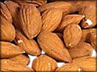 Photo of a pile of almonds with skin.