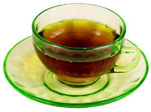 Both green and black tea is good for lowering cholesterol. Photo of green tea in green glass cup.