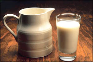 Whole milk products are high cholesterol foods: Picture of white milk jug and glass of milk.
