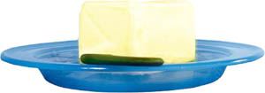 Butter is also a food high in cholesterol: Picture of big lump of butter on a blue plastic plate.