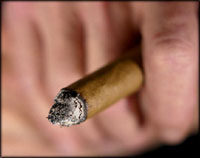 Picture of hand holding a smoking cigar og cigarette.