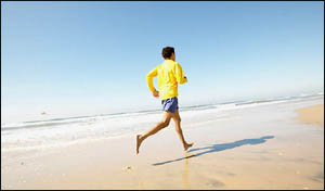 Lower your cholesterol with good exercise: Man running on the beach.